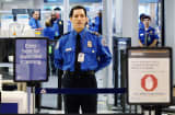 A TSA agent waits for passengers to use the TSA PreCheck lane being implemented by the Transportation Security Administration at Miami International Airport.