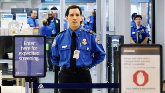 A TSA agent waits for passengers at the Miami International Airport.