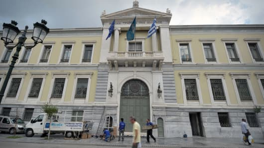 A man walks by the National Bank of Greece headquarters in Athens.