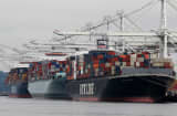 Container ships are positioned under cranes at the Port of Oakland