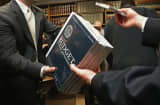 Senate Budget Committee staff members hand out copies of the Obama Administration&#039;s proposed FY 2014 federal budget in the Dirksen Senate Office Building on Capitol Hill.