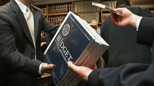 Senate Budget Committee staff members hand out copies of the Obama Administration's proposed FY 2014 federal budget in the Dirksen Senate Office Building on Capitol Hill.