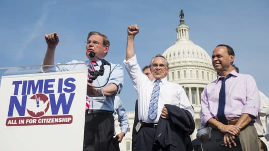 Sen. Robert Menendez, D-N.J., speaks to immigration reform supporters as Rep. Ruben Hinojosa, D-Texas, and Rep. Luis Gutierrez, D-Ill., listen during the National Rally for Citizenship on the west lawn of the U.S. Capitol.