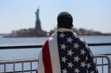Ecuadorian immigrant now living in the U.S. for 12 years, looks towards the Statue of Liberty while participating in a 'Time is Now' rally.