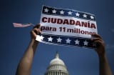 An immigration activist holds up a sign outside the Capitol during a rally.