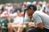Tiger Woods of the United States lines up a putt on the 18th hole during the first round of the 2013 Masters Tournament at Augusta National Golf Club