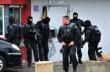 Members of Eris, a regional intervention unit  of the French penitentiary administration are at work in front of a door opened with explosives