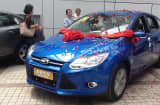 A family takes delivery of their new Ford Focus at a dealership in Chongqing, China.