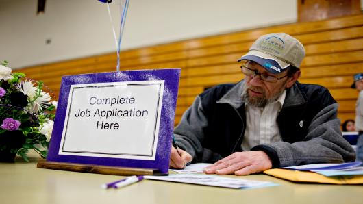 Job seeker Clinton Crouch, who said he was laid-off in Sept. 2011, fills out an application for a maintenance job during a job fair at Illinois Valley Community College (IVCC) in Oglesby, Illinois, U.S.