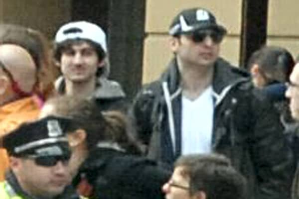 The two suspects in the Boston Marathon bombing walk near the marathon finish line.