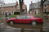 Residents of Des Plaines walk down a flooded sidewalk on a residential street in Des Plaines, Illinois.