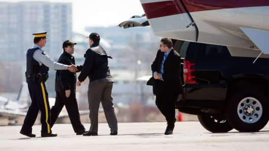 RCMP officer shakes hands to what appears to be pilots after a transfer of a terror suspect at Buttonville Airport, April 22, 2013.  Canadian security sources say they have thwarted a terrorism plot and arrested two suspects in Ontario and Quebec.