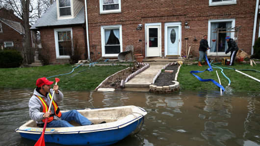 Octavio Castillo paddles a boat down a street to reach his cousin's home in Des Plaines, Ill., on April 19.