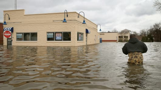Reyes Garcia wades through floodwater to inspect flood damage to a building April 19, 2013 in Des Plaines, Illinois.
