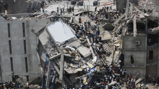 People rescue garment workers trapped under rubble at the Rana Plaza building after it collapsed, Bangladesh, India.