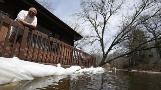 Joe Kozlowski looks out on his flooded property from his porch in Fox Lake, Illinois.