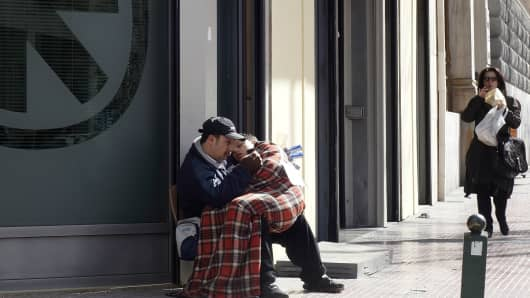 A father and son beg in front of Alpha bank at Panapestimiou Street in Athens.