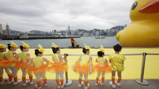 Rubber Ducky is given a warm welcome by young children from SDM Jazz and Ballet Academie at Victoria Harbour in Hong Kong.