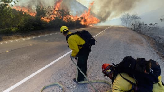 A firefighter sprays water on a flare up as a wildfire burns along the Pacific Coast Highway close to Naval Base Ventura County (NBVC) near Point Mugu, California May 3, 2013.