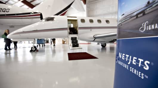 A Netjets Inc. sign stands hear a new Embraer Phenom 300 jet at Eppley Airfield in Omaha, Nebraska, U.S.