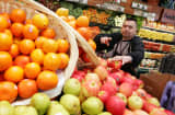 Whole Foods employee Cesar Martinez stocks shelves with apples at a Whole Foods Market