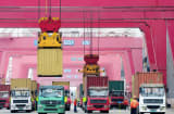 Shipping containers are transported in a port in Qingdao, east China&#039;s Shandong province.