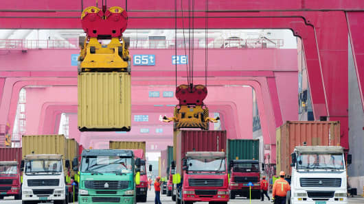 Shipping containers are transported in a port in Qingdao, east China's Shandong province.
