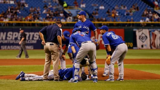 Teammates assist J.A. Happ after he was hit by a line drive on Tuesday.