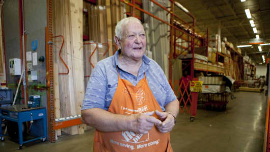 A senior citizen works as a sales associate at Home Depot in the lumber department.