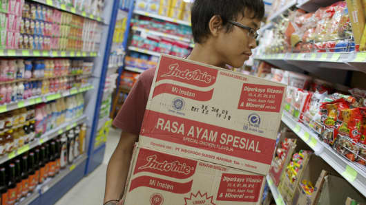 A shopper picks up two boxes of PT Indofood at a supermarket in Jakarta.