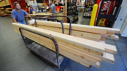 Construction worker Alex Sierra buys lumber for home framing at the Home Depot store.