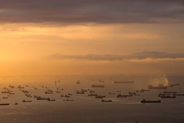 Boats in the Singapore Strait at dawn as seen from the Marina Bay Sands, a casino resort located by the Marina Bay in Singapore.