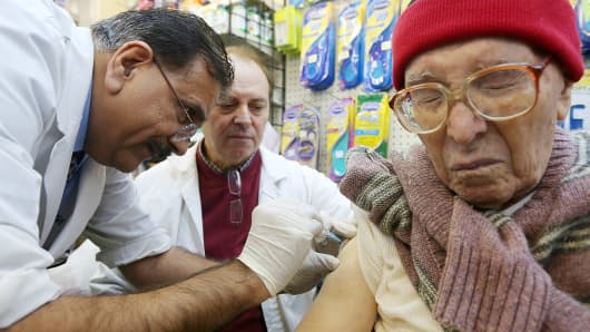 Chief pharmacist Ali A. Yasin (L) injects Juan Castro (R) with influenza vaccine as assistant Agripinno Camiolo looks on at New York City Pharmacy in Manhattan.