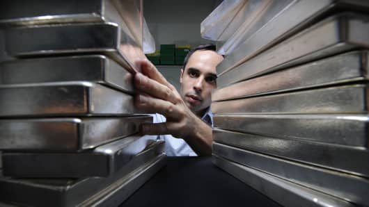 Gregor Gregersen, director of Silver Bullion Pte., arranges a stack of silver bullion bars.