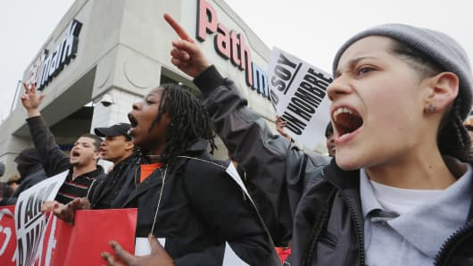People hold signs during a protest for better wages for fast food workers.
