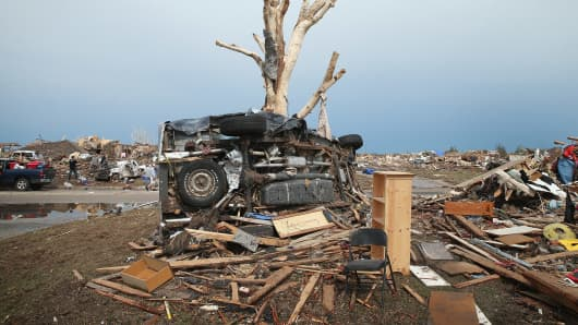 A pickup truck is wrapped around a tree after a powerful tornado ripped through Moore, Oklahoma.