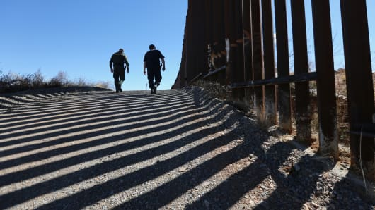 U.S. Customs and Border Protection personnel walk along a section of the recently constructed fence at the U.S.-Mexico border.
