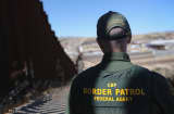 A U.S. Border Patrol agent looks along a section of the recently constructed fence at the U.S.-Mexico border.