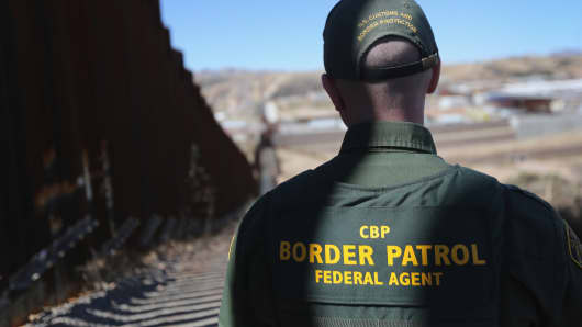A U.S. Border Patrol agent looks at a section of the U.S. - Mexico border.