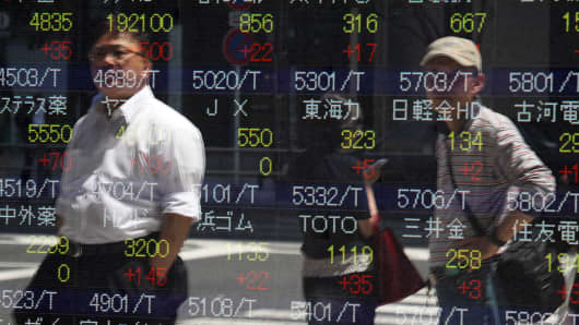 Pedestrian are reflected in an electronic stock board in Tokyo, Japan, on Friday, May 24, 2013.