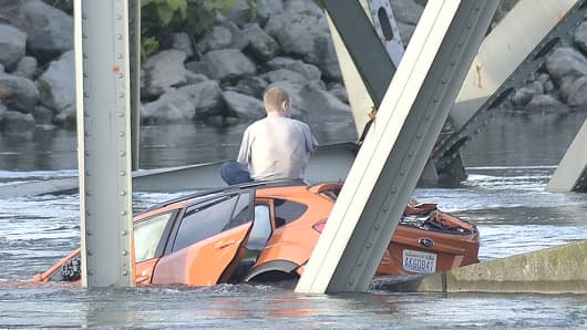 An unidentified man waits on his submerged vehicle in the Skagit River on Thursday.