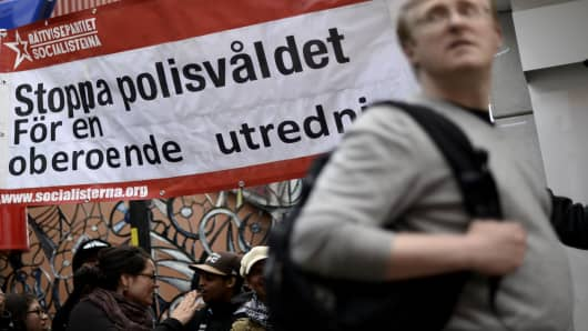 "A man passes by a banner reading ""Stop police violence for an independent investigation"" during a demonstration against police violence and vandalism in the Stockholm suburb of Husby this week."
