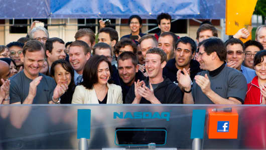 Mark Zuckerberg, CEO of Facebook, center, Sheryl Sandberg, COO, center left, and Robert Greifeld, CEO of Nasdaq OMX Group, center right, on IPO day on May 18, 2012.