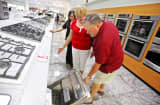 Sales representative Shieldeen Langley, left, assists shoppers looking for a dishwasher at the ABT store in Glenview,