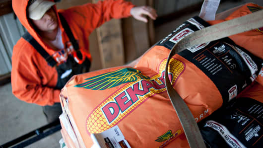 A farmer unstraps a delivery of Monsanto DeKalb brand seed corn on a farm in Princeton, Ill.