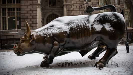 The Wall Street Bull, officially called Charging Bull, is covered in snow the morning after a snowstorm in New York City.