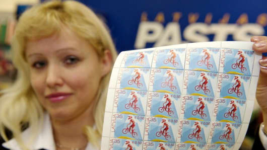 A post worker shows the first Latvian stamps denominated in both lats and euros in Riga on January 30, 2013.