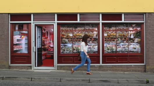 A pedestrian walks pass stickers applied to the windows of a former butcher's shop in Belcoo, Northern Ireland, outside Enniskillen on June 1, 2013.