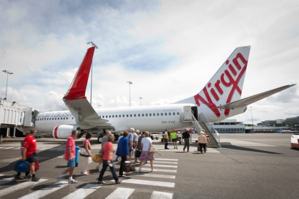 Passengers walk to board a Virgin Australia Boeing 737-800 aircraft at Sydney airport, Australia