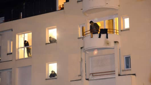 Migrants look at their windows in a former retirement house while gendarmes prepare to evacuate them